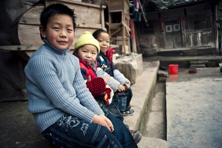 Sichuan, China - February 2: Three children sitting at home in rural China, February 2, 2011, in rural Sichuan Province, three rural children, in their own yard to play at home, watching the camera smiling Stock Photo - 12768773