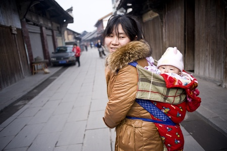 SICHUAN,CHINA - FEBRUARY 17: Unknown woman carried the baby, because the city transformation, farmers lose arable land, into the city looking for a job,  February 17, 2011,Sichuan, China Stock Photo - 12768855