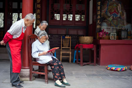 chanting: SICHUAN,CHINA-JULY 22,2010: Several unnamed elderly people in the temple chanting book, many local elderly people to Buddhism, July 22, 2010, shot in Sichuan Province, China Editorial