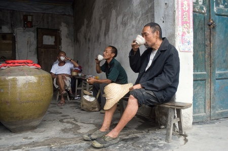 SICHUAN,CHINA-JULY 22,2010: unknown guests with drink, drink locally produced sorghum, July 22, 2010, shot in the Ancient Town of Sichuan Province, China
