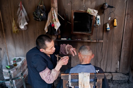 CHENGDU,CHINA-APRIL 24, 2011:unknown disability barber Barber for the guests, locals like to go here for a haircut, we are willing to help him, April 24, 2011 Stock Photo - 12768681