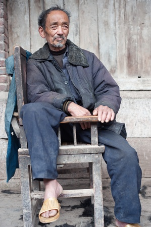 SICHUAN,CHINA-APRIL 4,2010:unknown elderly sitting on a chair, April 4, 2010, Sichuan Province, China, where many elderly people alone at home, the children are working in the field. Stock Photo - 12768564