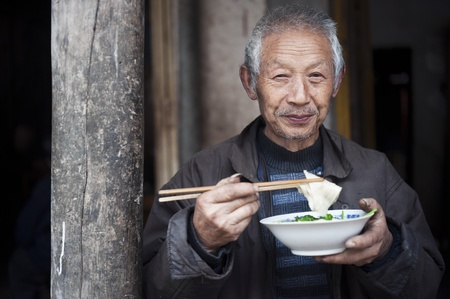 QIJIANG,SICHUAN, CHINA - APRIL 4, 2010:unnamed villagers are dining, the camera smiling, Sichuan Province, China, April 4, 2010. Many elderly people live like this Editorial