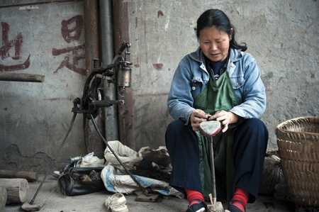 diverted: QIJIANG,SICHUAN, CHINA - APRIL 4, 2010:unnamed villagers are roadside shoe repair, April 4, 2010, Sichuan Province, China. Many people lose their farmland, diverted business.