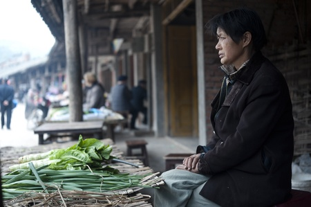 diverted: QIJIANG,SICHUAN, CHINA - APRIL 4, 2010: unnamed villagers are selling vegetables, Sichuan Province, China, April 4, 2010. Many people lose their farmland, diverted business. Editorial
