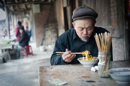 quo: QIJIANG,SICHUAN, CHINA - APRIL 4, 2010:unnamed villagers are dining, Sichuan Province, China, April 4, 2010. Many elderly people live like this.