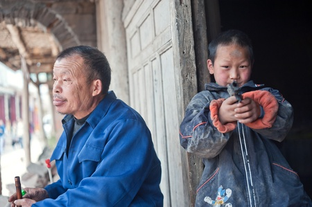 SICHUAN,CHINA-APRIL 4,2010:unknown old man and his grandson,April 4, 2010, sichuan province, China, the local old man help with child, and the child all parents work elsewhere