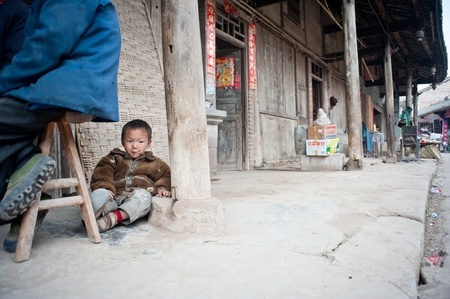 SICHUAN,CHINA-APRIL 4,2010:Unnamed small boy sitting on the floor playing, his parents are working in the field, upbringing by his grandfather, Sichuan, China, April 4, 2010 Stock Photo - 12768574