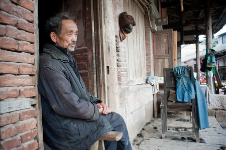 SICHUAN,CHINA-APRIL 4,2010:The nameless barber sitting in his shop, due to loss of arable land, in order to survive, local farmers diverted business, Sichuan, China, April 4,2010 Stock Photo - 12768596