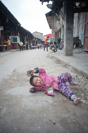 SICHUAN,CHINA-APRIL 4,2010:Unknown on the floor crying, her parents are working in the field, upbringing by his grandfather, Sichuan, China, April 4,2010 Stock Photo - 12768513