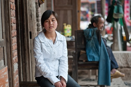 SICHUAN,CHINA-APRIL 4,2010:The nameless girl sitting on her father's barber shop, due to the loss of arable land, in order to survive, local farmers diverted to do business, Sichuan, China, April 4, 2010 Stock Photo - 12768524