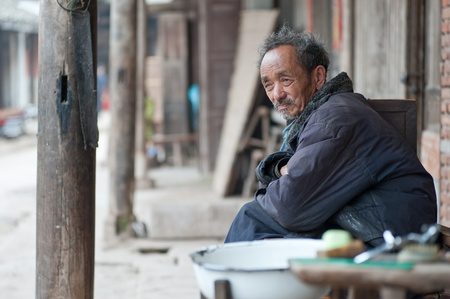 diverted: SICHUAN,CHINA-APRIL 4,2010:Nameless old man and his barber shop by the side of the road, due to loss of arable land, in order to survive, local farmers diverted to do business, Sichuan, China, April 4, 2010