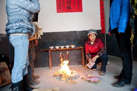 vals geld: Sichuan, China -22 januari 2012, een onbekende vrouw, tijdens de Lente Festival brandende Mingbi, offers om overleden familieleden Sichuan, China, 2012 22 januari Redactioneel
