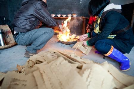 dinero falso: Sichuan, China -22 de enero de 2012, una mujer desconocida, durante la Fiesta de Primavera, la quema Mingbi sacrificios a sus familiares muertos en Sichuan, China, 2012 January 22, Editorial