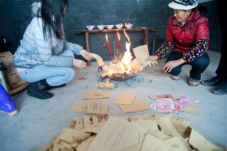 dinero falso: Sichuan, China -22 de enero de 2012, una mujer desconocida, durante el Festival de Primavera de la quema Mingbi, las ofrendas de los sacrificios a los parientes muertos de Sichuan, China, 2012, 22 de enero