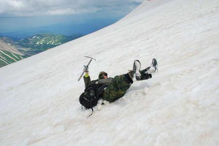 rockclimber: The tourist slides on snow from mountain. Stock Photo