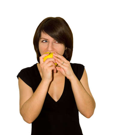 The girl in a black dress eats a yellow apple Stock Photo