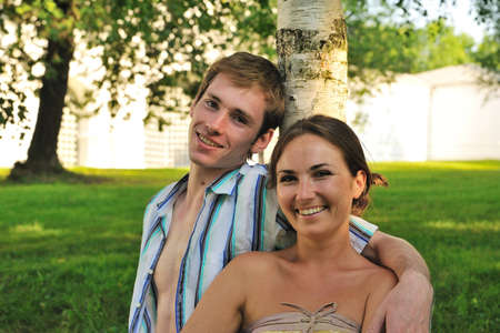 this photo shows a young couple near a tree Stock Photo