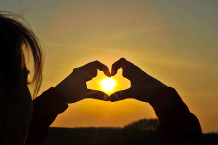 Hands making heart with the sun inside Stock Photo - 7630267