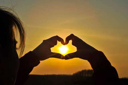 corazones azules: Manos haciendo el coraz�n con el sol dentro de