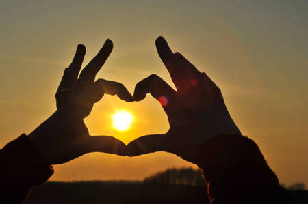 Hands making heart with the sun inside Stock Photo