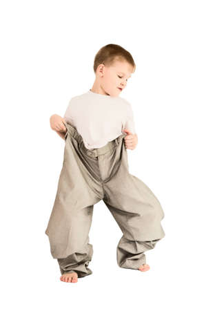 This photograph shows a boy in fathers trousers Stock Photo