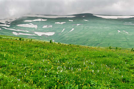 Summer landscape with green grass, mountains and clouds photo