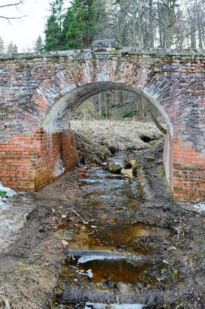mud pit: Garbage in river under bridge
