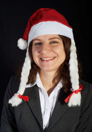 beautiful woman in a Santa Claus hat on black background Stock Photo