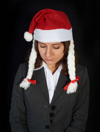 beautiful woman in a Santa Claus hat on black background photo