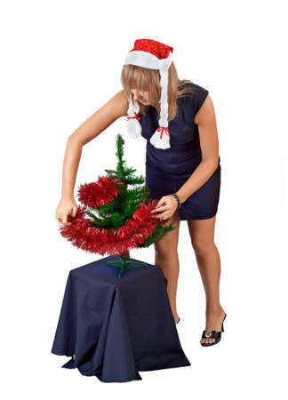 beautiful girl in the hat of Santa Claus dress up the Christmas tree