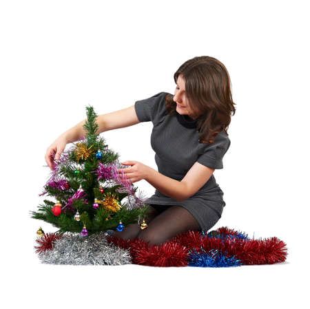 young girl decorates the Christmas tree on a white background Stock Photo
