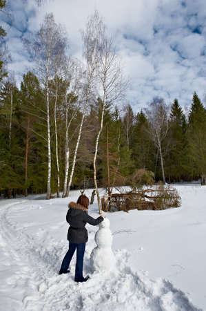 attractive girl makes a snowman Stock Photo