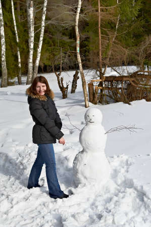 attractive girl standing beside a snowman