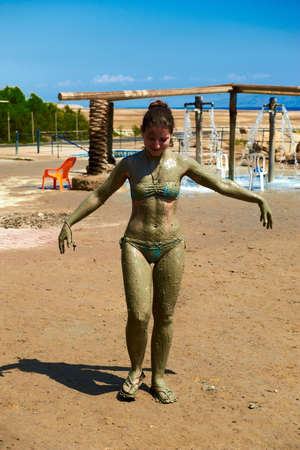 Smiling Caucasian woman is applying mud from the Dead Sea on the beach in Israel photo