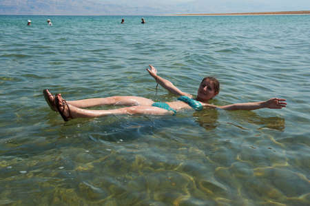 Caucasian woman floating in the waters of the Dead Sea in Israel