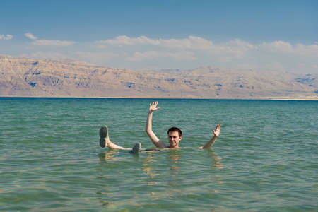 Caucasian man floating in the waters of the Dead Sea in Israel Stock Photo