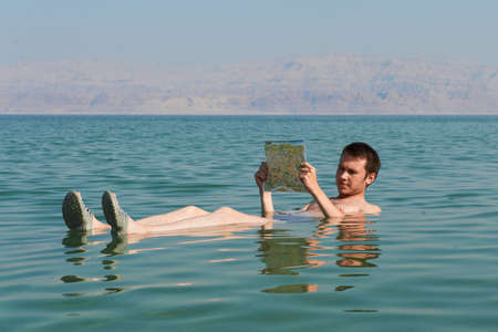 Caucasian man reads a book floating in the waters of the Dead Sea in Israel photo