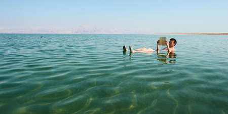 and israel: Caucasian man reads a book floating in the waters of the Dead Sea in Israel Stock Photo