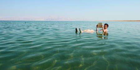 Kaukasischen Mann liest ein Buch schwimmt in den Gewässern des Toten Meeres in Israel Standard-Bild