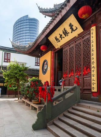 future buddha: Chinese monastery decorated with red ribbons desires at the entrance and in the trees Editorial