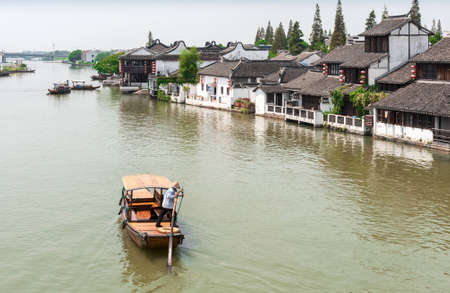 zhouzhuang: ZHOUZHUANG-AUGUST 19: Tourists walk near the monastery in the village on the water, on August 19,2012, Zhouzhuang, China Editorial