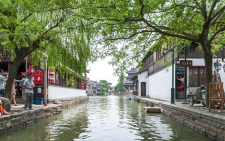 zhouzhuang: ZHOUZHUANG-AUGUST 19: Tourists walk along the canals in the village on the water, on August 19,2012, Zhouzhuang, China Editorial