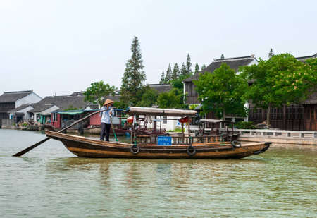 zhouzhuang: ZHOUZHUANG-AUGUST 19: Chinese gondolier sailing on a boat in the village on the water, on August 19,2012, Zhouzhuang, China