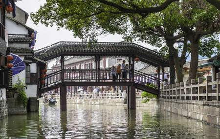 zhouzhuang: ZHOUZHUANG-AUGUST 19: Tourists walk on the bridge in the village on the water , on August 19,2012, Zhouzhuang, China Editorial