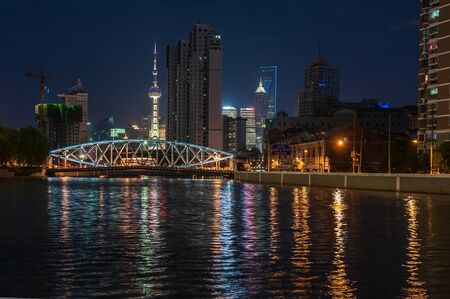 night view of the city, the bridge over the river and the lights reflected in the water