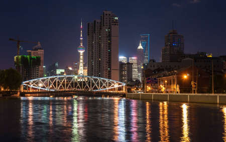 night view of the bridge across the river and the lights reflected in the water