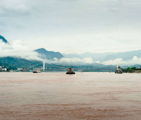 yangtze river: Travel by boat on the Yangtze River with a view of the mountains and the town