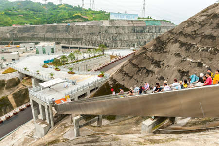 SANDOUPING-AUGUST 21: Tourists walk down the escalator with a viewing platform Three Gorges Dam, on August 21,2012, Sandouping, China Stock Photo - 16377799