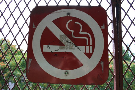 No smoking sign on a chain link fence.
